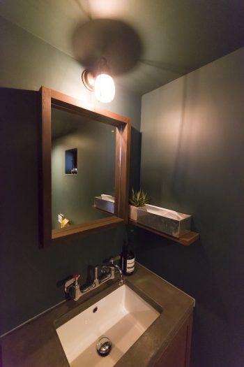 1階の洗面所。絵美香さんの好きなショップを参考にしたそう。深みのあるグリーンの壁がポイント。1階も2階も壁付き蛇口で、メンテナンスを考慮した。