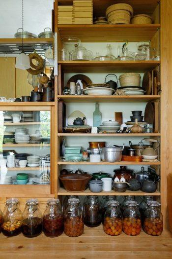 たくさんの皿や調理道具が収納されている。下の瓶は梅やスモモ、パイナップルなどのシロップ漬け。農作業の合間に炭酸水で割って飲む。