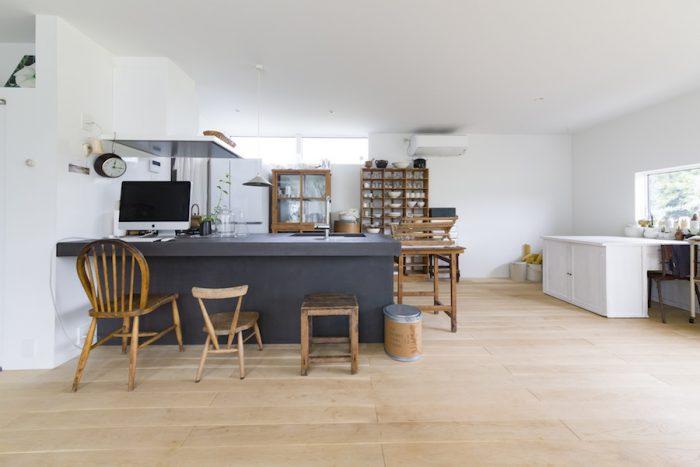 モールテックス仕上げの味わいのあるキッチン台は、真っ白な空間を引き締める。照明はtamiser。