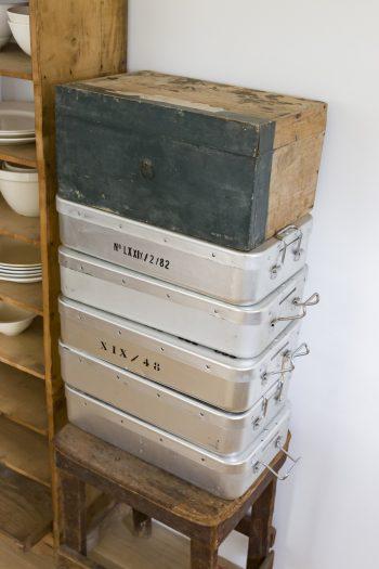 キッチンの収納にはアルミや古材のボックスなどを使用。ガラス食器や陶器ともうまく調和する。