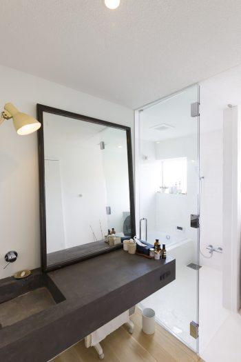 ガラス張りで明るいバスルーム。洗面台もモールテックス仕上げに。