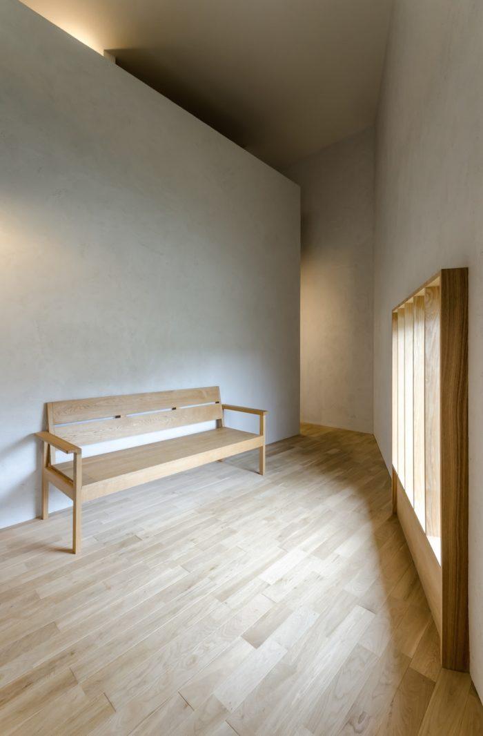 大きな開口の前にベンチがひとつ置かれた1階リビング。壁の面構成にはアート的な空気感も。