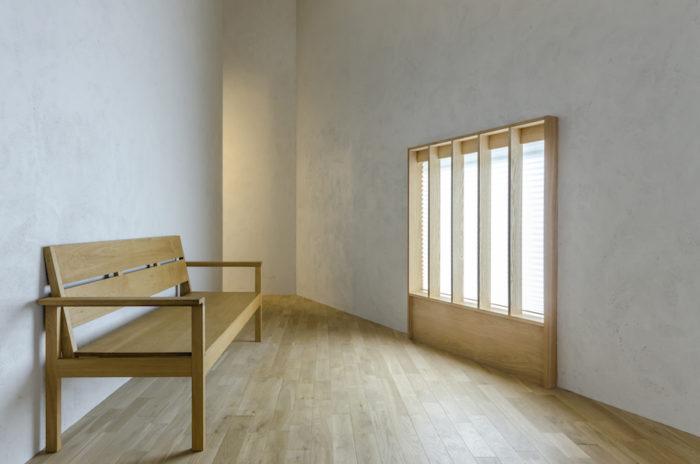 ベンチの位置からは外が見えるが、ダイニングからは、ルーバーがあるため光だけが見える。開口廻りの枠材はアルミサッシを隠している。ベンチは家具作家の傍島浩美さんによるもので、オブジェ的にも鑑賞できるようデザインされている。