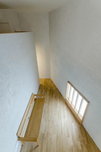 2 階からリビングを見下ろす。リビングの形状には、台形の敷地形状が反映している。
