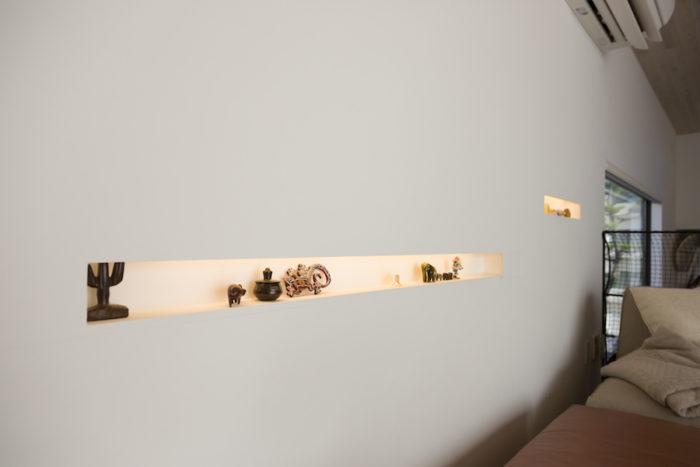 壁にお気に入りの小物を飾れるスペースを作った。中の照明器具は調光機能がついている。