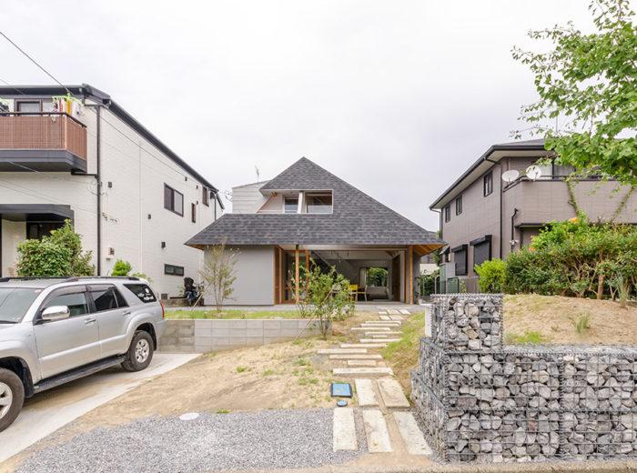 左右の家よりも高さが抑えられているが、屋根面は大きい。将来の増築を見込んで敷地の手前右側のスペースが開けられている。