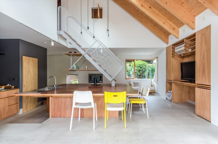 部屋の中心部分に置かれた約3m四方の大きなテーブル。その端部から2階へと階段が架けられている。キッチン部分は土間よりも少し低めにつくられコルクが敷かれている。