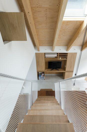 階段部分を見下ろす。屋根に開けられた開口からテーブル部分に光が落ちる。