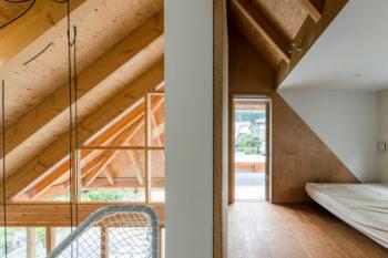 奥に屋根を支える大きなトラス(三角形の構造体)の存在が確認できる。右奥にバルコニーがある。