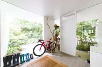 開口部が大きく取られた玄関は、明るく開放的。モルタル敷きの土間のような雰囲気。
