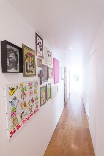 玄関から一直線に伸びる廊下。アーティストやお子さんたちの作品が飾られてギャラリーのよう。