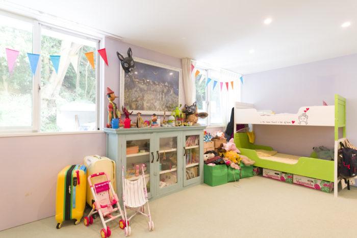 色彩があふれ、創造性に富んだ子供部屋。後ろの山の木々も鮮やか。