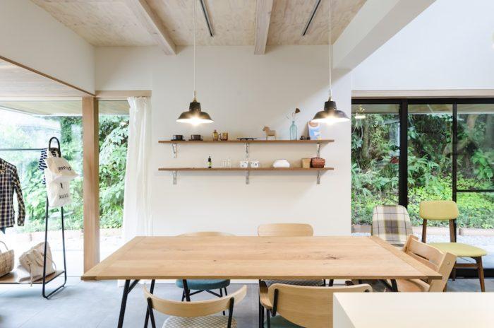 1 階部分に軒を回すことで、緑の見え方をコントロール。同時に、下部に土間をつくり、内部空間を延長して見せている。ダイニングのテーブルとイスはイデーの製品。