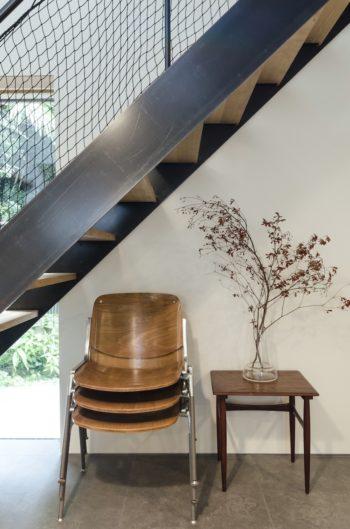 階段下のスタックされた椅子もさりげなくしゃれた雰囲気をつくり出す。