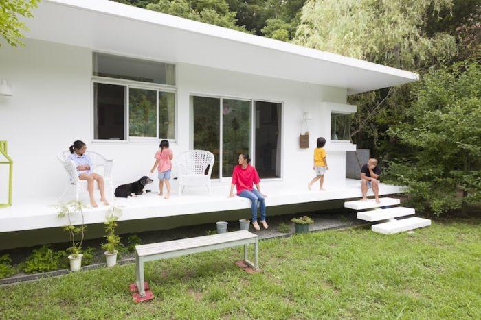 屋根に凹凸のない平屋の贅沢な造り。湿気対策のため、床は地面から少し上げられている。窓を開け放てば風が通り抜け夏も心地よい。