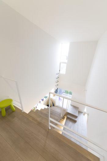 2階から土間スペースの吹き抜けを見る。軽やかな階段が採光や通風を邪魔しない。
