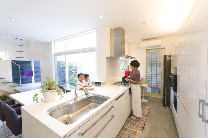 会話が弾む対面式のキッチンは、真っ白で機能的。通路側も広めに取り、家族や友人が一緒に作業できる仕様にした。