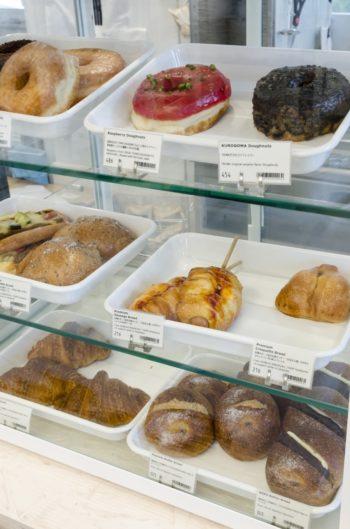 GOOD TOWN DOUGNUTのドーナツの中には、TRUNK(STORE)オリジナルの黒ごまのドーナツも。渋谷の障がい者支援施設「まる福」から届く惣菜パンも並ぶ。