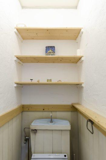 腰板と同じ板を貼ったタンク、木の棚、漆喰の壁と、凝った装飾のトイレ。