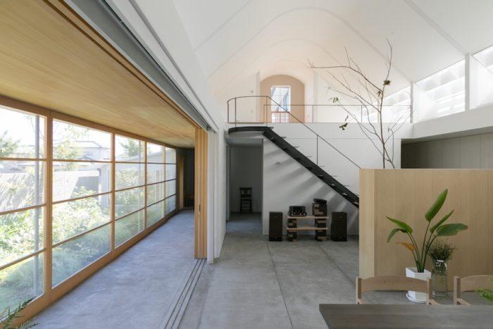 玄関から1階全体を見渡す。左手のテラスが内と外をつなぐ役割を果たす。中央奥の椅子が置いてあるスペースは主寝室。
