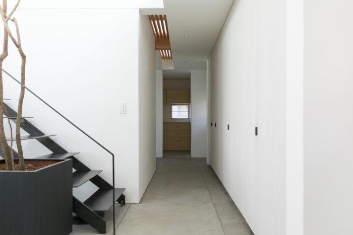 キッチンからユーティリティは側廊でつながる。2階予備室の床の一部をスノコにし、側廊に光を落としている。