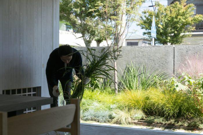 庭の植物を生ける聡さん。庭は定期的に橋内さんに手入れを依頼している。
