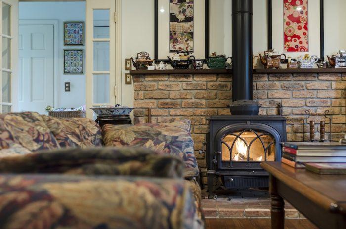 薪ストーブはノルウェーのヨツール社製。煙突の左右にご主人のお宮参りの時の着物と、ケイティーさんの七五三の時の着物の生地を額装して飾っている。