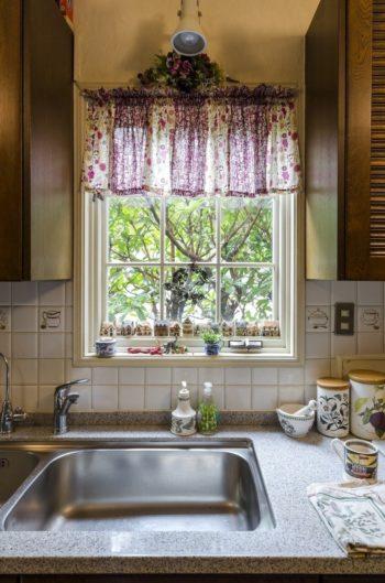 出窓は季節ごとにディスプレイを変更。リバティ生地でつくる自作のカーテンも付け替える。庭の植物もラフに飾って楽しむ。