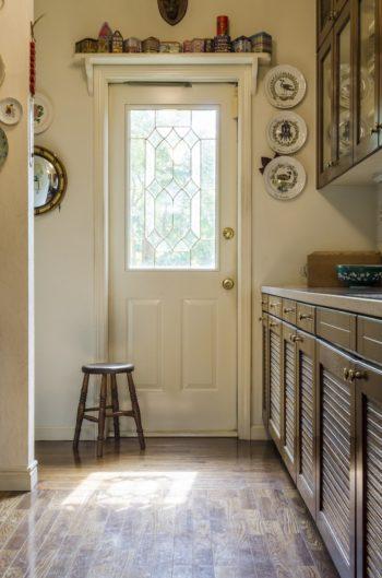 庭の緑を切り取る勝手口のドア。ドア枠の上には、家の形をした紅茶缶だけを集めてディスプレイ。