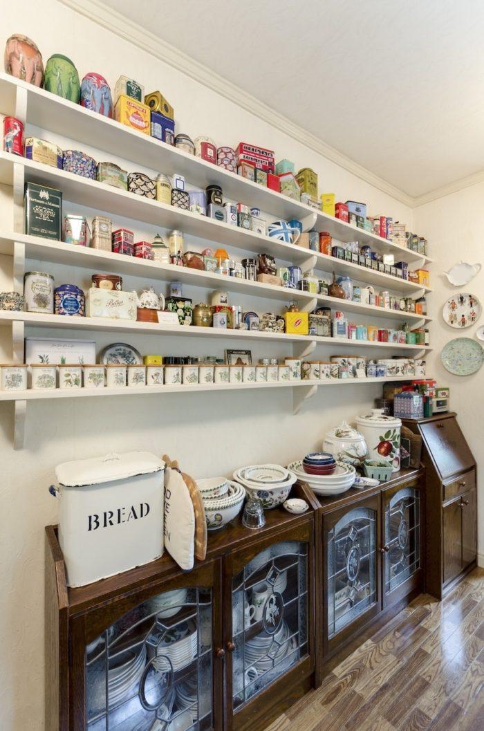 キッチン背面に紅茶缶の飾り棚を設置。大工さんが3段、ご主人が2段取り付けた。「もう1段つけたいけれど、危ないから無理ね」。
