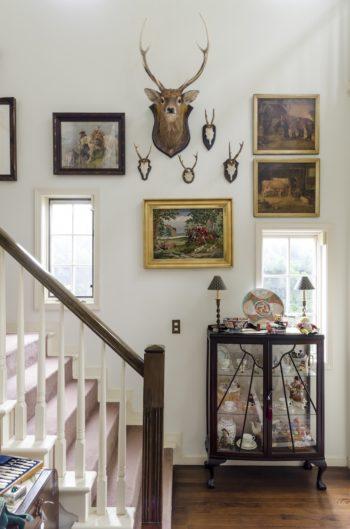 鹿の壁飾りやアンティークの刺繍絵画が壁面を彩る。レイアウトの仕方にもセンスが光る。