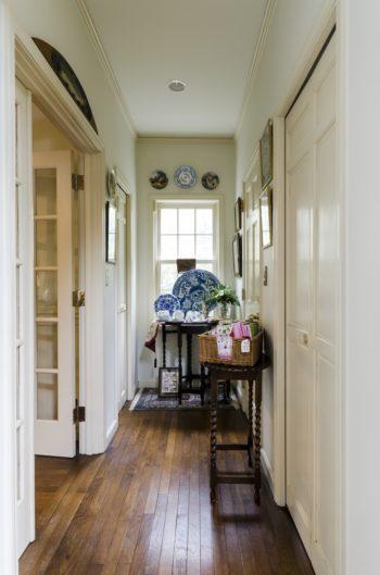 玄関からリビングへ続く廊下。ギャラリーを兼ねて、食器やファブリックをディスプレイ。