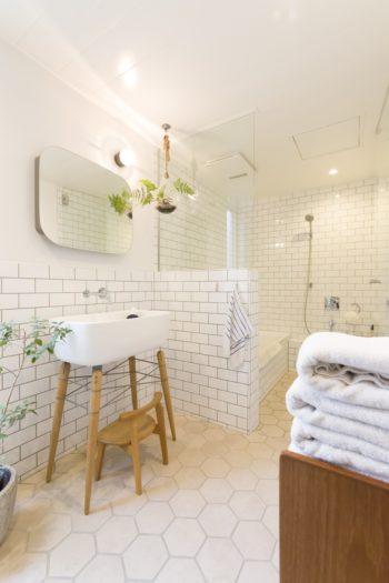 壁はサブウェイタイル、床は六角形のタイルを組み合わせている。鏡も個人輸入したもの。鏡をスライドすると棚が現れる。天井から下げたボトルではシノブを育てている。繊細な葉が美しい。