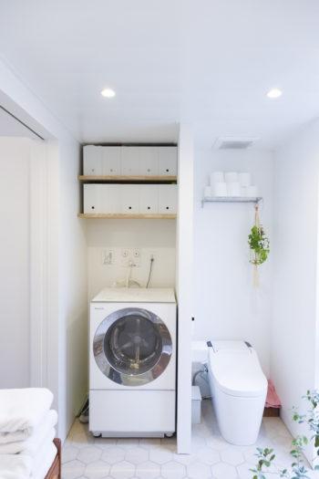 トイレもユーティリティスペースの一角に。洗濯機の上の収納はボックスの色を統一してすっきりと見せている。