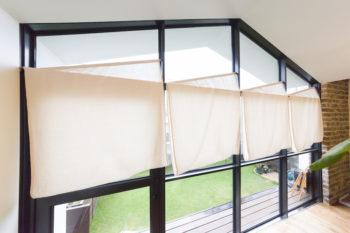 格子の窓にカーテンはつけていないけれど、夜など目隠しをしたいときは、布を暖簾のようにかけて使う。