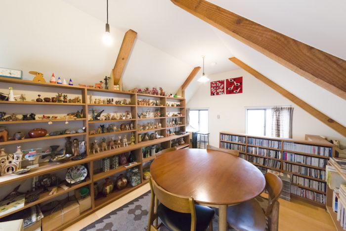 ロフトだった3階を趣味のスペースに。空間にしっくりなじんだテーブルと椅子は、北欧のヴィンテージ。フォークアートを並べた棚は、ひとつひとつが映えるよう、背面を白く塗ってもらった。