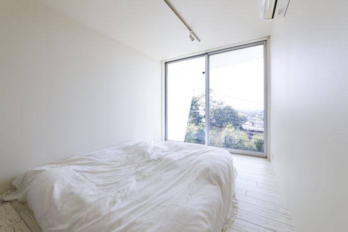 2階の家族の寝室。イメージしているベッドに出会えていなく、現在は仮のものだそう。床はパイン材、壁はややアイボリーがかった色味にし、リラックスできるよう配慮。ちなみに1階の壁はグレーがかった色味でシャープに仕上げた。