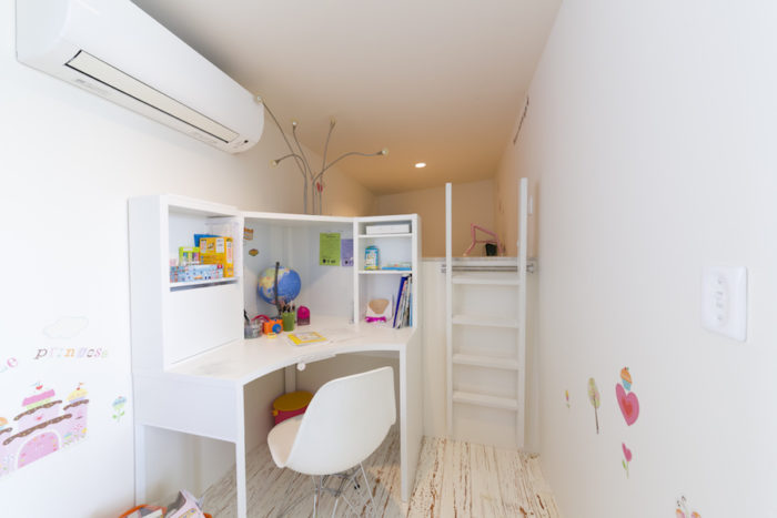 長女の部屋。奥さまが描かれた壁の絵が可愛らしいアクセントになっている。奥のロフトの下が玄関。