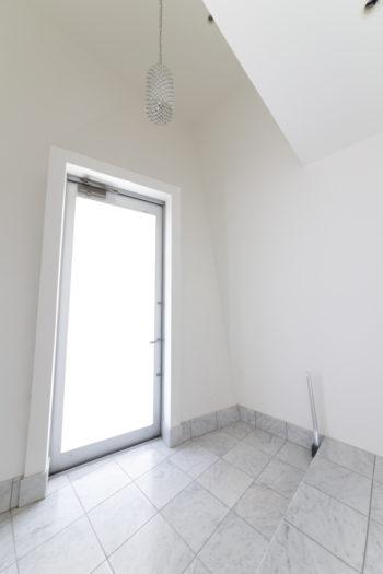 窓のない玄関のため、天井を高くし、扉は曇りガラスにして光を取り込んでいる。光沢のある壁面は、特殊加工により立つところによって見え方が変わる。