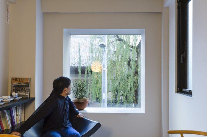 2階のダイニングから外の柳の木を見る川久保さん。外の景色が絵のように見えるよう、サッシを設けずにスチールの出窓を外壁に取り付けている。階高が低いため道路との距離が近いが、出窓にすることにより外から内部が見づらくなっている。