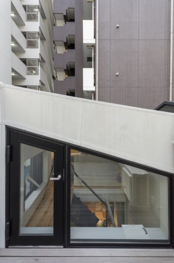 屋上からロフトと3階の子ども室を見る。背後には高層のマンションが建つ。
