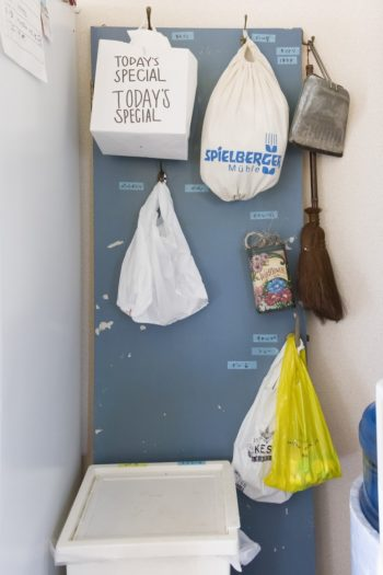 思い出のドアをリメイクして再利用。掃除道具の保管、ゴミの仕分けにも味がある。