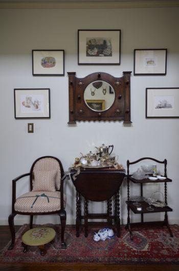 写真中央は、鏡とコートハンガーを兼ねた実用的でデザイン性の高い英国家具。それを囲むように絵画を飾るアイディアはさすが。