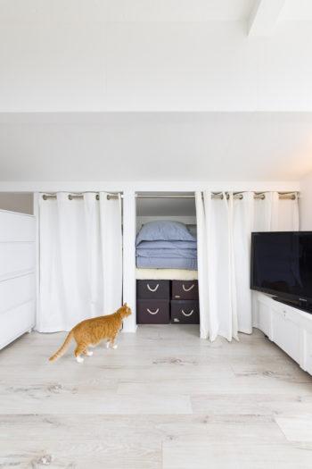 収納は一カ所に集約。扉はつけずに、お手製のカーテンで仕切った。テレビ台は古い木箱を白く塗ったもの。