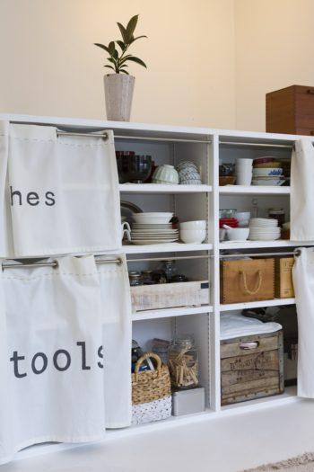 """造作の棚にお手製のカーテンを取り付けた。""""dishes"""" 、""""Tools""""など、収納しているものをステンシルで明記。工具も沢山揃えている。"""