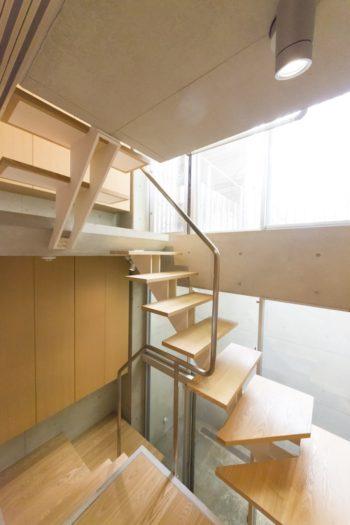 軽やかな階段にスタイリッシュな手すりがアクセント。各階段の踊場は収納スペースに。窓の奥がドライエリア。