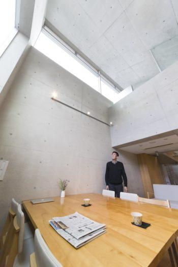 地上部分の吹き抜け。身長180cmの近藤さんが床から約7mの天井を見上げる。近藤さんの頭の上がサニタリールーム。