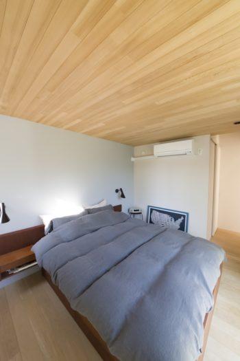 寝室の天井は板張りにして落ち着いた雰囲気。壁の一面を薄いブルーにペイント。