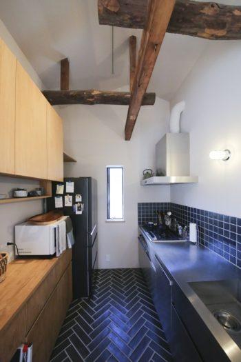キッチンにも古い梁が。白い壁とのコントラストが素敵。壁のタイルは美濃焼。シンクと一体型のカウンターはステンレス。