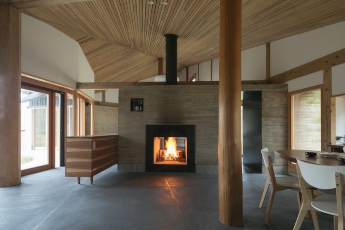 キッチンからダイニングを見る。正面には厚さ1.2メートルの版築壁に埋め込んだ暖炉がある。冬はこの暖炉が住まいの主役となる。梁より上を開けることで、開放的な空間を実現した。